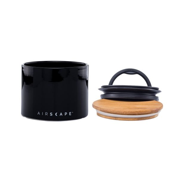 Photo of a black ceramic coffee storage container with a wooden and black plastic lid next to container.