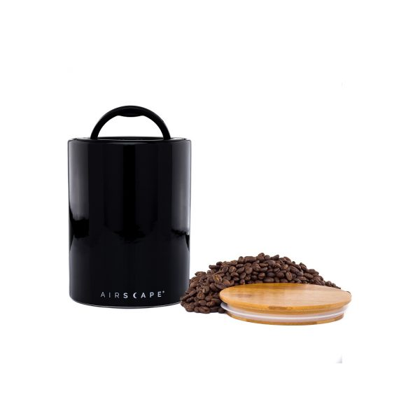 Photo of a black coffee storage container with a wooden lid and whole coffee beans sitting next to it.