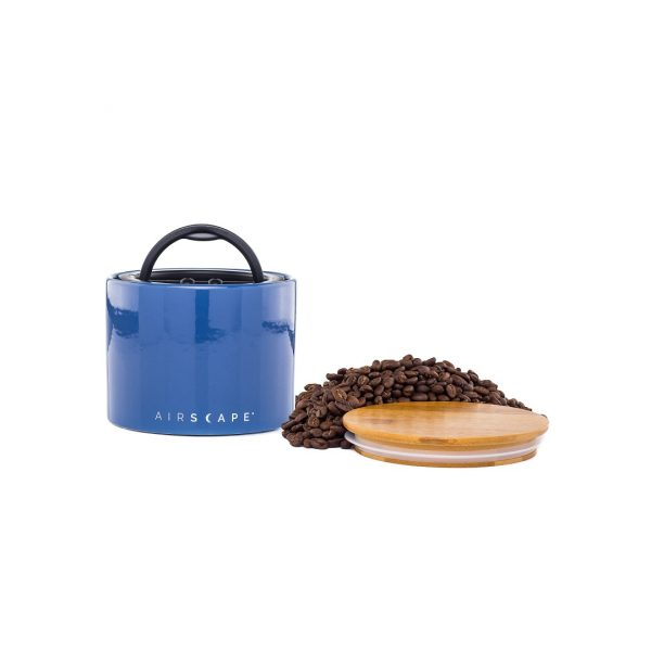 Photo of a blue ceramic coffee storage container with wooden lid and whole coffee beans.