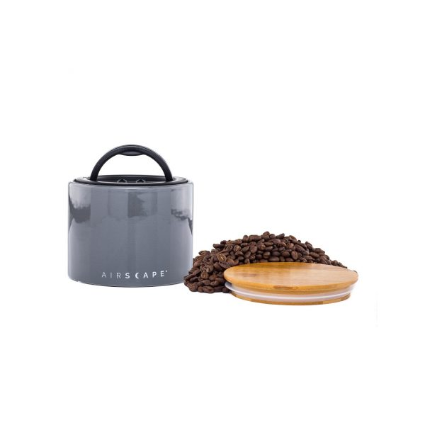 Photo of grey coffee storage container and the wooden lid and whole coffee beans next to container.