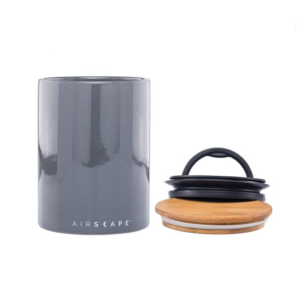 Photo of a grey coffee storage container with two lid setting next to it.
