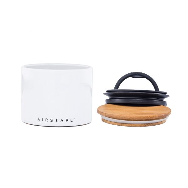Photo of a white airscape ceramic coffee storage container with a wooden and black plastic lid.