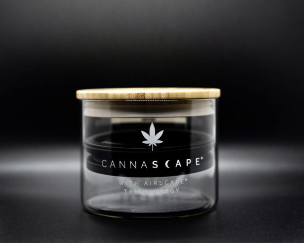 Photo of Cannascape Glass Canister with wooden top lid, and inner Airscape lid with soft lighting in front of a black background