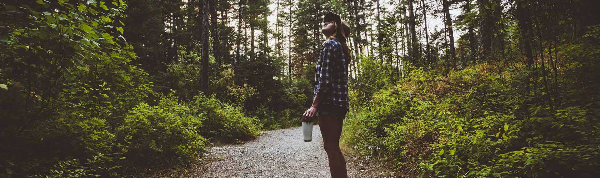 Photo of girl on forest trail with white tumbler